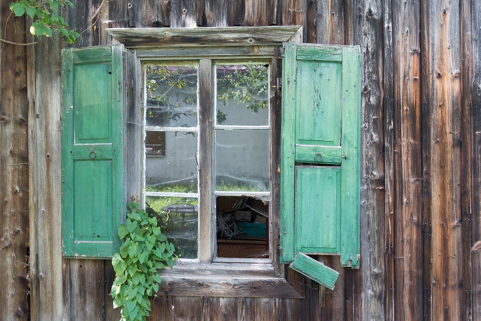 Spring maintenance on your cabin includes fixing broken shutters and checking windows.