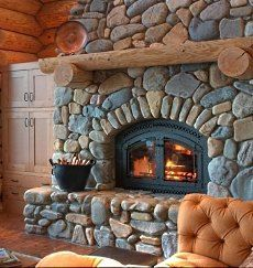 Cabin fireplace with round riverstone surround.