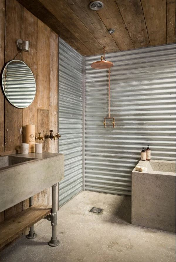 Cabin bathroom with concrete counter and copper shower head.