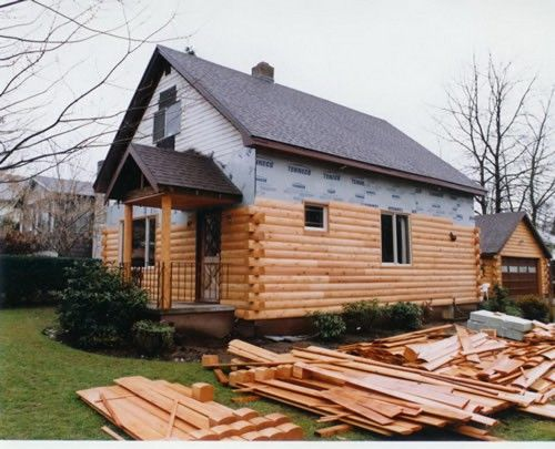 Log siding being installed on the exterior of a house.