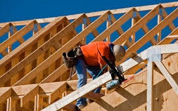 Log home loan image showing home under construction.
