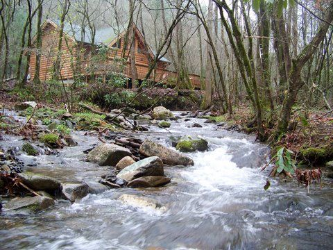 Stream rushing past log cabin in the woods.