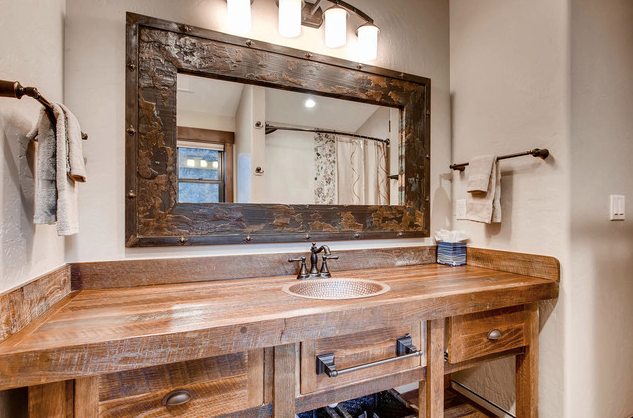 Woden counter and wood mirror frame in cabin bathroom.